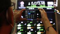 Seorang pria mengambil gambar layar yang menampilkan informasi pergerakan saham di gedung Bursa Efek Indonesia, Jakarta, Senin (8/6/2020). Seiring berjalannya perdangan, penguatan IHSG terus bertambah tebal hingga nyaris mencapai 1,50 persen.   (Liputan6.com/Angga Yuniar)