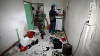 Petugas menyisir sebuah rumah lokasi penggerebekan peredaran narkoba di Kampung Ambon, Jakarta, Rabu (24/1). Penggerebekan dilakukan untuk mengamankan penyalahgunaan narkotika yang kerap dilakukan di Kampung Ambon. (Liputan6.com/Arya Manggala)