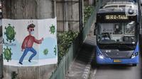 Bus transjakarta melintasi mural bertema protokol kesehatan Covid-19 yang menghiasi tiang pancang jalan tol di Jalan Ahmad Yani, Jakarta, Minggu (13/12/2020). (merdeka.com/Iqbal S. Nugroho)