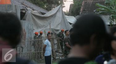 Sejumlah personel TNI AU berjaga di lokasi helikopter jatuh yang sudah di tutup terpal di Dusun Kowang, Sleman (8/7). Heli jatuh setelah melakukan penerbangan dari Solo menuju Yogyakarta. (Liputan6.com/Boy Harjanto)