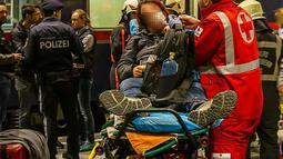 Seorang penumpang mendapatkan perawatan dari tim medis usai dua gerbong kereta bertabrakan di Salzburg, Austria (20/4). Dua gerbong kereta penumpang di Austria bertabrakan saat akan dipasangkan menjadi satu rangkaian. (FMT/Wolfgang Moser/APA/AFP)