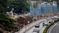 Kendaraan melintas disamping pembangunan proyek kereta ringan LRT di Jalan HR Rasuna Said, Kuningan, Jakarta, Rabu (20/12). Proyek yang saat ini dalam proses pemasangan tiang tersebut ditargetkan selesai Desember 2018. (Liputan6.com/Faizal Fanani)