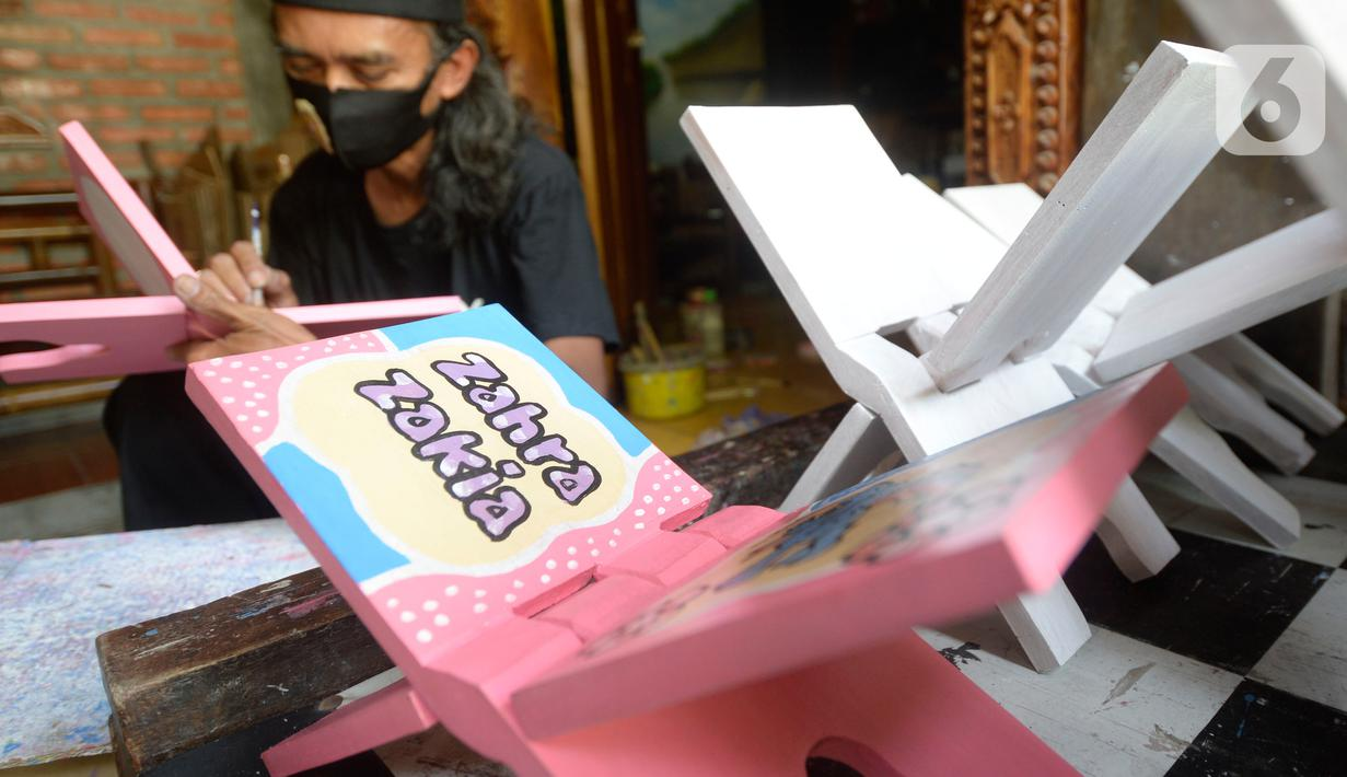 Perajin, Seno (47), menyelesaikan lukisan rekal atau tatakan Al Quran untuk anak-anak di Perumahan Gading Depok, Curug, Bojongsari, Depok, Jumat (25/09/2020). Di masa pandemi, tatakan Al Quran dan talenan lukis yang dijual seharga Rp 50 ribu mengalami penurunan pemesanan. (merdeka.com/Dwi Narwoko)