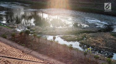 Warga beraktivitas di sekitar aliran Kanal Banjir Timur yang mengalami kekeringan, kawasan Duren Sawit, Jakarta, Selasa (3/9/2019). Kemarau panjang yang melanda Ibu Kota menyebabkan debit air Kanal Banjir Timur berkurang hingga menampakkan dasar kanal. (Liputan6.com/Immanuel Antonius)