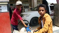 """Seorang anak mengisi bahhan bakar di distrik Abs utara, Yaman, (8/5). Perwakilan UNICEF di Yaman, Meritxell Relano mengatakan generasi anak-anak di Yaman menghadapi masa depan yang suram karena tidak ada akses ke pendidikan."""" (AFP Photo/Essa Ahmed)"""