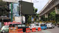 Kendaraan melintas di depan sebuah videotron di simpang Jalan Iskandarsyah, Jakarta Selatan, Minggu (2/10). Garis polisi terpasang terkait insiden videotron itu yang sempat memutar tayangan porno pada Jumat, 30 September 2016. (Liputan6.com/Helmi Afandi)