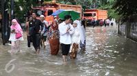 Pengantin Mansur dan Maya melintasi banjir usai melakukan akad nikah di KUA Mampang Prapatan, Jakarta, Selasa (21/2). Walapun banjir sepasang pengantin ini tetap melakukan akad nikah. (Liputan6.com/Herman Zakharia)