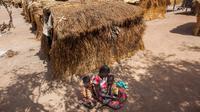 Nybol Madut duduk bersama anak-anaknya di tempat penampungan di Sudan Selatan (22/11). Mereka menderita krisis air bersih dan kelaparan karena minimnya persediaan pangan. (AFP Photo/Albert Gonzalez Farran)