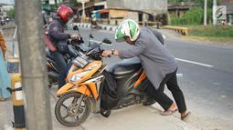 Pengendara mendorong motornya menerobos separator untuk memutar balik di Jalan Raya Pantura, Palimanan, Cirebon, Jawa Barat, Jumat (7/6/2019). Ditutupnya sejumlah jalur putar balik menyebabkan warga nekat menerobos separator untuk memersingkat waktu tempuh. (Liputan6.com/Immanuel Antonius)