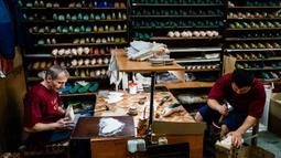 Para pekerja menyelesaikan pembuatan sepatu pointe di bengkel perusahaan Grishko, Moskow, Rusia, 25 Februari 2020. Sepatu buatan Grishko dijual ke seluruh dunia dan menghiasi panggung-panggung balet dunia. (Dimitar DILKOFF/AFP)