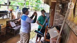 Petugas PLN memeriksa kWh meter listrik usai banjir melanda perumahan Ciledug Indah, Tangerang Baten, Senin (21/2/2021). Petugas PT PLN (Persero) mulai mendatangi tiap-tiap rumah di seluruh Indonesia untuk memeriksa kWh meter listrik prabayar. (Liputan6.com/Angga Yuniar)
