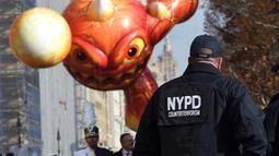 Petugas Kepolisian Kota New York mengawasi mengawasi Parade Thanksgiving Day di New York City (26/11/2015). Beragam balon raksaksa yang dibuat seperti tokoh animasi menjadi suguhan utama dalam perayaan tersebut. (AFP Photo/Timothy A. Clary)