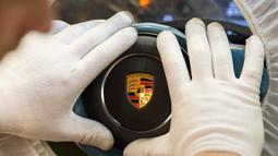 Karyawan merakit bagian kemudi mobil Porsche di pabrik Porsche di Stuttgart, Jerman (26/1). Untuk pemberian bonus kepada karyawannya ini Porsche merogoh kocek lebih dari Rp 2,7 triliun. (AFP Photo/Thomas Kienzle)