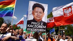 Pengunjuk rasa membawa berbagai atribut saat memprotes pemerintahan baru Polandia yang dipegang oleh partai konservatif di Warsaw, Sabtu (7/5). Massa mengepung Ibu Kota guna menuntut perubahan hukum dan peradilan yang baru dibuat. (REUTERS/Kacper Pempel)