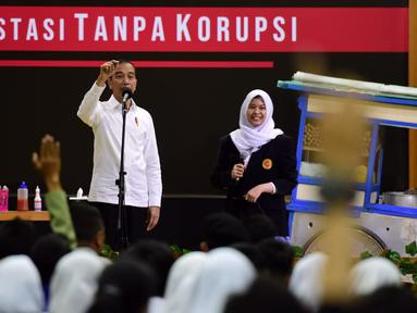 Presiden Joko Widodo (kiri) berbincang dengan murid seusai menyaksikan drama bertajuk Prestasi Tanpa Korupsi di SMKN 57 Jakarta, Jakarta Selatan, Senin (9/12/2019). Kegiatan tersebut dalam rangka memperingati Hari Antikorupsi Sedunia. (Liputan6.com/Biropres Kepresidenan)