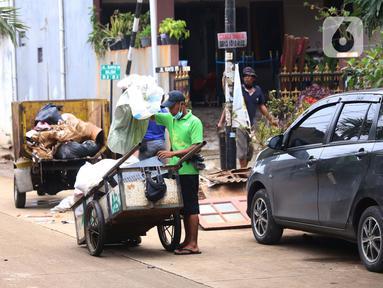 Pengumpul barang bekas mencari barang rusak akibat banjir di Ciledug Indah, Tangerang, Banten, Senin (21/2./2021). Pasca banjir melanda perumahan tersebut menjadi berkah bagi para pengumpul barang rongsok karena banyak barang yang di buang pemilik rumah. (Liputan6.com/Angga Yuniar)