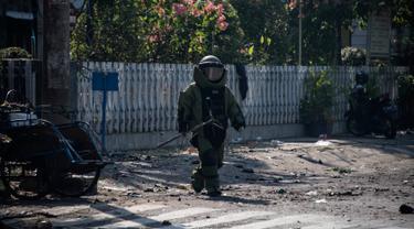 Tim Gegana menyisir lokasi bom meledak di halaman kompleks gereja di Surabaya, Jawa Timur, Minggu (13/5). Ledakan terjadi di tiga gereja, yakni Santa Maria di Ngagel, GKI di Jalan Diponegoro dan sebuah gereja di Jalan Arjuna. (AFP/JUNI KRISWANTO)