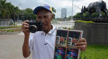 Fotografer taman, Joel Estrella berpose dengan kameranya di sebuah taman di Manila, Filipina (22/4). Estrella telah bekerja sebagai fotografer taman sejak tahun 1970. (AFP Photo/Ted Aljibe)