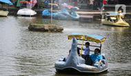 Wisatawan menaiki perahu saat mengunjungi TMII, Jakarta, Kamis (20/8/2020). Libur panjang yang bertepatan tahun baru islam di manfaatkan masyarakat bersama keluarga  berlibur ke sejumlah tempat wisata. (Liputan6.com/Faizal Fanani)