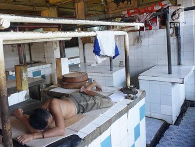Warga menggunakan kios sebagai tempat tidur di Pasar Cipete Jakarta, Sabtu (10/8/2019). Rencana revitalisasi 21 pasar tradisional di Jakarta yang ditargetkan rampung pada 2021 terancam molor lantaran hingga kini status lahan pasar masih dalam proses perubahan sertifikasi. (Liputan6.com/Angga Yuniar)