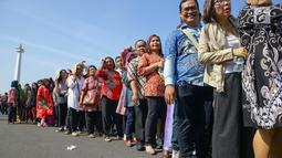 Warga mengantre di kawasan Silang Monas, untuk mengikuti Open House Jokowi di Istana Kepresidenan, Jakarta Rabu (5/6/2019). Antrean warga sejak pagi hari terlihat mengular hingga lebih dari 20 meter di pintu sebelah barat Monas. (Liputan6.com/HO/Grandy)