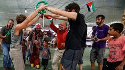 Anak-anak Palestina bermain dengan rombongan badut Spanyol yang tampil menghibur di desa suku Bedouin, Tepi Barat, 22 September 2018. Atraksi ini dilakukan lantaran desa di dekat permukiman Israel itu akan digusur Israel pada Oktober. (AFP/ABBAS MOMANI)