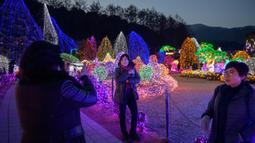Gambar yang diambil 11 Januari 2020, pengunjung melihat tampilan beragam kerlip lampu di Garden of Morning Calm, sebelah timur Seoul di distrik Gapyeong, Korea Selatan. Festival cahaya tahunan tersebut dinikmati saat musim dingin, Desember sampai akhir bulan Maret. (Ed JONES / AFP)