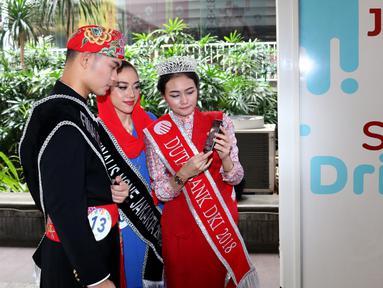 Duta Bank DKI Jakarta 2018, Nita Indriani memberikan edukasi layanan transaksi non tunai melalui aplikasi JakOne Mobile kepada finalis Abang None DKI Jakarta 2018 di Vending Machine Bank DKI di Balaikota, Jakarta (26/07). (Liputan6.com/HO/Budi)