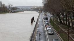 Sejumlah kendaraan melintas di samping sungai Seine yang meluap, Paris, Prancis (5/1). Meluapnya air di sungai Seine akibat tidak mampu menampung debit air setelah hujan terjadi terus-menerus. (AFP Photo/Ludovic Marin)