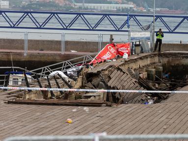Petugas penyelidik memeriksa lokasi  platform panggung dari kayu yang roboh pada festival musik di barat laut Spanyol, Senin (13/8). Insiden di tengah acara tersebut mengakibatkan 316 orang terluka, 9 di antaranya dalam kondisi serius. (AFP/Carmelo Alen)