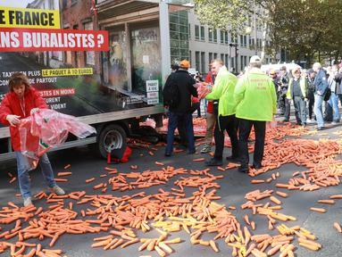Para penjual tembakau melempar wortel ke jalan saat melakukan aksi protes rencana kenaikan harga sebungkus rokok di Paris, Rabu (4/10). Pemerintah Prancis merencanakan kenaikan harga untuk sebungkus rokok pada 2020 mendatang. (AFP PHOTO/JACQUES DEMARTHON)