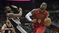 Pemain Atlanta Hawks, Paul Millsap (kanan) menggiring bola melewati hadangan pemain Spurs, Jonathon Simmons pada lanjutan NBA basketball game di Philips Arena, (01/01/2017). Atlanta menang 114-112. (AP/John Amis)