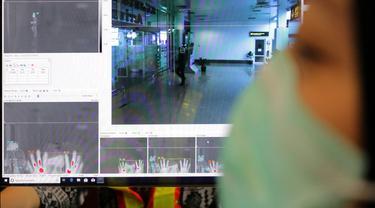 Petugas kesehatan memindai suhu tubuh penumpang di bandara Depati Amir di Pangkal Pinang di pulau Bangka Belitung (24/1/2020). Sejumlah negara mengantisipasi penyebaran virus corona dari China. (AFP Photo/Anindira Kintara)