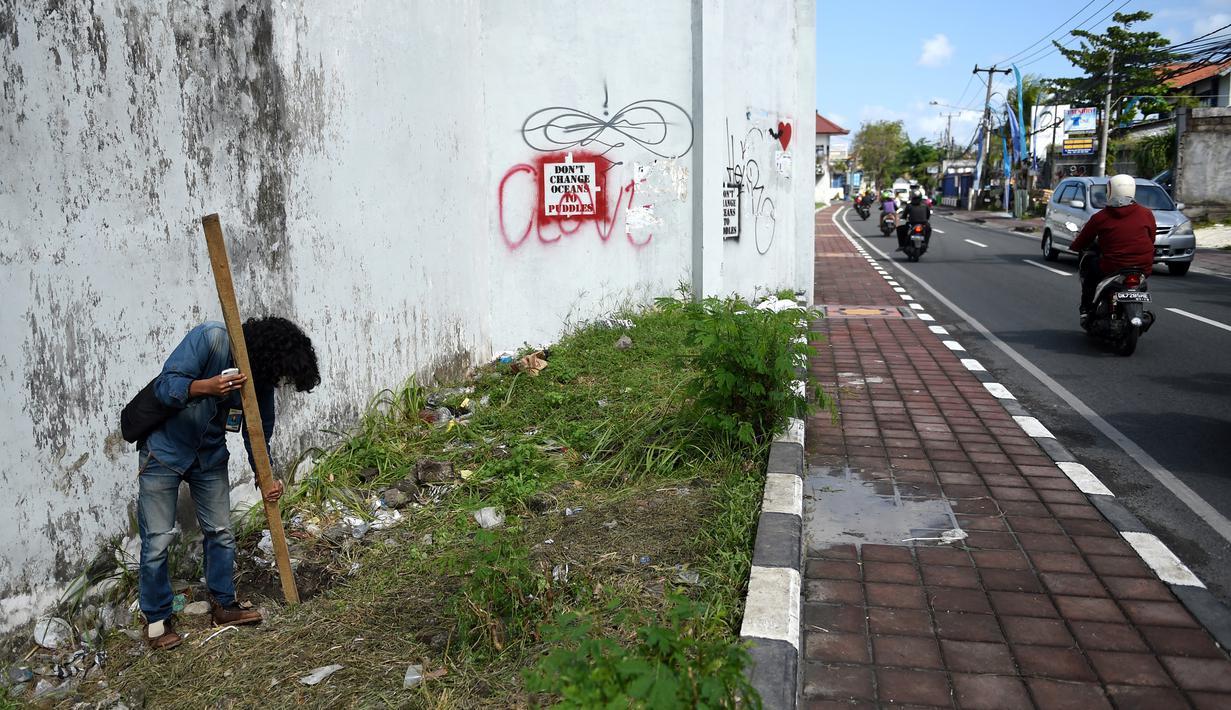 Seorang jurnalis memeriksa lubang yang digunakan narapidana asing untuk kabur dari Lapas Kerobokan, Bali, Senin (19/6). Empat narapidana asing kabur masih diburu petugas setelah meloloskan diri dari lapas melalui terowongan tersebut. (SONNY TUMBELAKA/AFP)