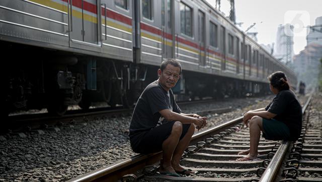 Warga mengobrol sembari berjemur di bantaran rel di kawasan pemukiman padat Pejompongan, Jakarta, Selasa (6/7/2021). Berjemur diri di bawah matahari di antara pukul 08.00-11.00 WIB merupakan salah satu upaya sederha menjaga kesehatan selama pandemi virus COVID-19. (Liputan6.com/Faizal Fanani)