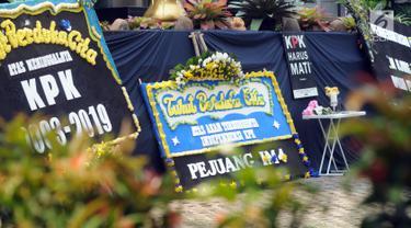 Sejumlah karangan bunga diletakkan dekat kain hitam besar yang menutupi logo KPK di Gedung Merah Putih, Jakarta, Senin (9/9/2019). Keberadaan kain hitam dan karangan bunga ini merupakan bentuk protes atas revisi Undang-undang KPK yang dinilai dapat melemahkan KPK. (merdeka.com/Dwi Narwoko)