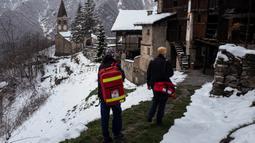 Petugas medis berjalan dari rumah ke rumah saat melakukan kampanye vaksinasi virus corona COVID-19 Moderna untuk penduduk berusia di atas 80 tahun di Elva, Lembah Maira, dekat Cuneo, Italia barat laut, 17 April 2021. (MARCO BERTORELLO/AFP)