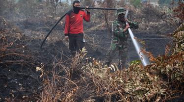 Prajurit TNI dan petugas Badan Penanggulangan Bencana Daerah (BPBD) berusaha memadamkan kebakaran hutan dan lahan di Kabupaten Kampar, Provinsi Riau (12/9/2019). Titik api kebakaran yang terjadi di Indonesia telah melonjak tajam. (AFP Photo/Adek Berry)