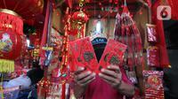 Pedagang menunjukkan angpao Imlek dagangannya di kawasan Tangerang, Sabtu (6/2/2021). Pandemi virus corona COVID-19 membuat para pedagang pernak-pernik Tahun Baru Imlek di kawasan tersebut mengeluh karena menurunnya penjualan dibandingkan tahun-tahun sebelumnya. (Liputan6.com/Angga Yuniar)