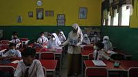 Guru membagikan lembar soal kepada sejumlah murid SDN Kota Baru saat ujian penilaian akhir sekolah di SDN Kota Baru 3 Bekasi, Jawa Barat, Senin (8/6/2021). Ujian yang dilaksanakan secara tatap muka tersebut diikuti kelas 4 dan 5. (Liputan6.com/Herman Zakharia)