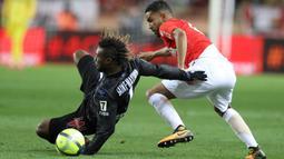 Pemain Nice, Allan Saint-Maximin (kiri) jatuh saat melewati adangan pemain Monaco, Jorge (kanan) pada lanjutan Ligue 1 di Louis II Stadium, Monaco, (16/1/2018). AS Monaco bermain imbang 2-2 dengan Nice. (AFP/Valery Hache)