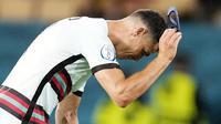 Bintang Timnas Portugal, Cristiano Ronaldo, tak mampu menutupi kekecewaan usai timnya didepak Belgia pada babak 16 besar Euro 2020. (AP/Thanassis Stavrakis, Pool)
