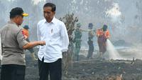 Presiden Joko Widodo berbincang dengan Kapolri Jenderal Tito Karnavian usai meninjau lokasi Karhutla Riau. (Liputan6.com/Istimewa/M Syukur)