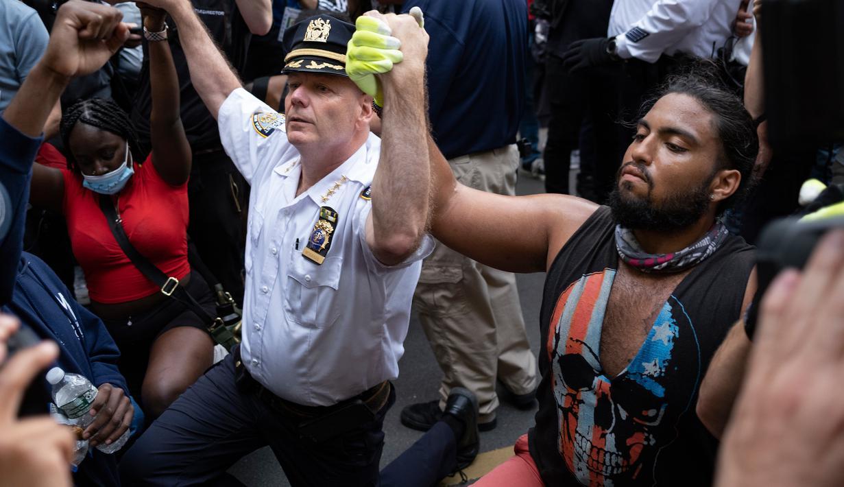 Kepala Departemen Kepolisian Kota New York, Terence Monahan berlutut bersama pengunjuk rasa dalam aksi protes kematian George Floyd, Senin (1/6/2020). Unjuk rasa besar melanda Amerika atas kematian pria kulit hitam yang tak bisa bernafas karena tercekik lutut polisi saat ditangkap. (AP/Craig Ruttle)