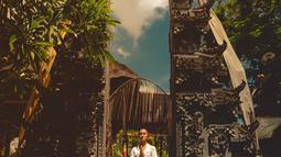 Mempelajari budaya Bali saat di sana, pesona Agnez Mo ketika mengenakan busana adat Bali mencuri perhatian saat berpose di gapura.  Ia mengenakan kebaya renda warna putih yang dipadukan dengan jarit warna ungu. (Liputan6.com/IG/@agnezmo)