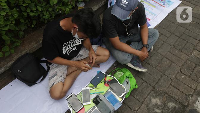 Penjual jasa perbaikan telepon genggam memperbaiki HP di trotoar jalan Mayjen Sutoyo depan Mall Pusat Grosir Cililitan (PGC), Jakarta, Rabu (14/7/2021). Kios yang biasa mereka tempati tutup seiring penutupan Mall PGC selama pemberlakuan PPKM Darurat Jawa-Bali. (Liputan6.com/Helmi Fithriansyah)
