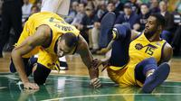 Dua pemain Utah Jazz, Rudy Gobert (kiri) dan Derrick Favors (15) jatuh saat berebut bola dengan pemain Boston Celtics pada lanjutan NBA basketball game di TD Garden, Boston, (15/12/2017). Utah Jazz menang 107-95. (AP/Michael Dwyer)