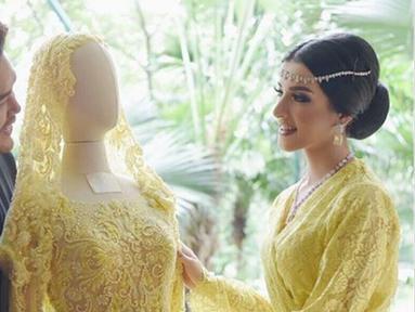 Selebgram Tasya Farasya berpose dengan gaun pengantin berwarna kuning karya desainer Ivan Gunawan bersama. Gaun pengantin tersebut dibuat Ivan untuk momen pernikahan Tasya. (Instagram/ivan_gunawan)
