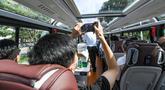 Seorang pria mengambil foto di dalam sebuah bus wisata di Shenzhen, Provinsi Guangdong, China selatan (22/10/2020). Shenzhen pada Kamis (22/10) meluncurkan tiga jalur bus wisata bagi wisatawan, yang masing-masing menampilkan budaya, teknologi, dan pemandangan malam kota tersebut. (Xinhua/Mao Siqian)