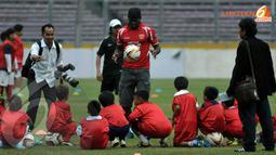 Louis Saha (tengah) memeragakan aksi dribling bola di hadapan peserta coaching clinic (Liputan6.com/ Helmi Fithriansyah)